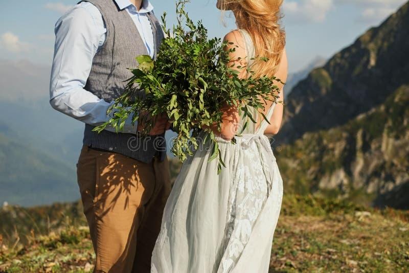 la jeune mariée a fermé ses yeux et chuchote quelque chose à son fiancé, bouquet en gros plan et vert sur le fond des montagnes photo stock