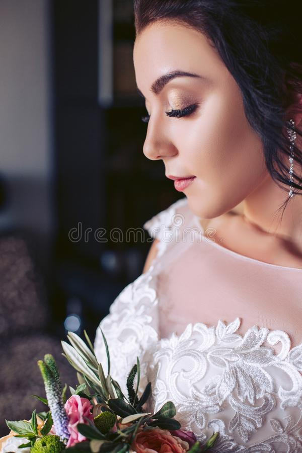 La jeune mariée a fermé ses yeux Support avec un bouquet des fleurs photographie stock