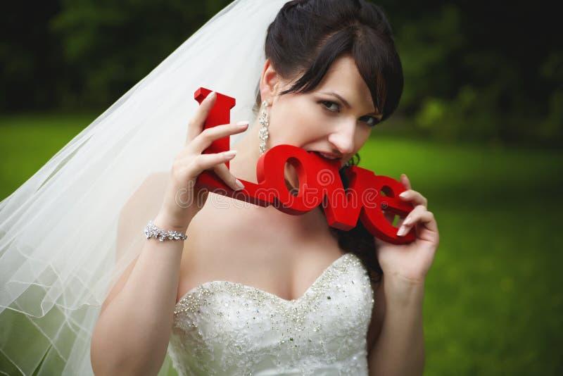 La jeune mariée gaie mord les lettres en bois du rouge photo stock