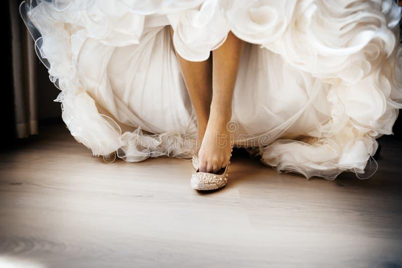 La jeune mariée habille des chaussures de mariage image libre de droits