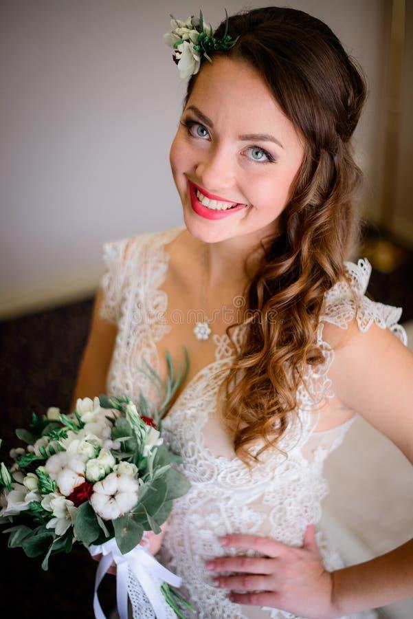 La jeune mariée heureuse avec de beaux yeux bleus pose dans la chambre d'hôtel riche photo stock
