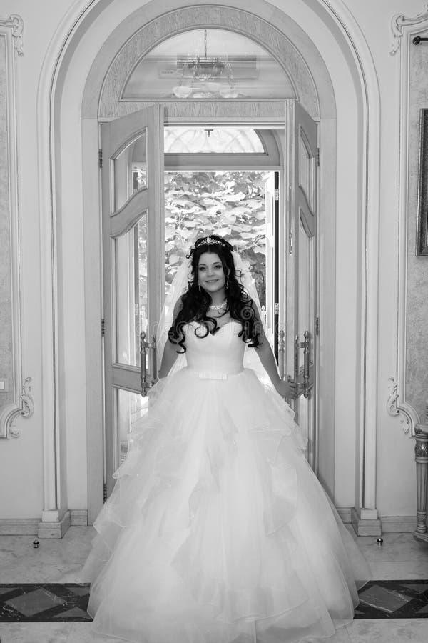 La jeune mariée heureuse entre dans la porte photos libres de droits