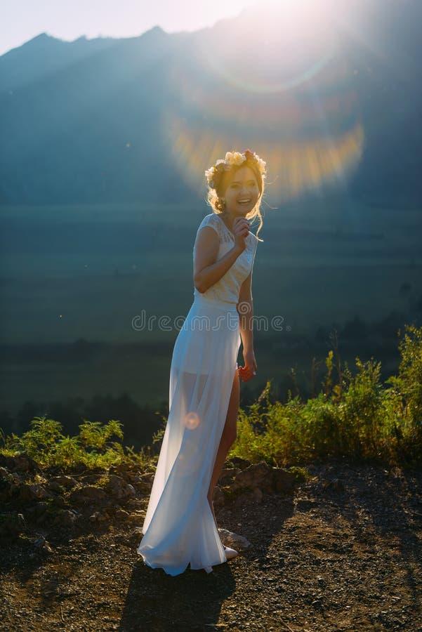 La jeune mariée heureuse magnifique avec la guirlande des fleurs dans une robe transparente rit aux rayons du soleil et à l'arr image libre de droits