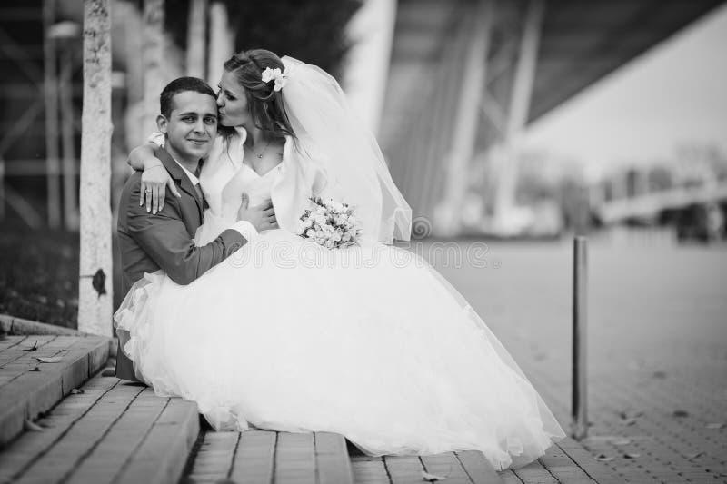 La jeune mariée heureuse magnifique de brune et le marié élégant dans le costume bleu s'asseyent photographie stock