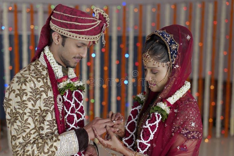 La jeune mariée indoue indienne et toilettent un couple de sourire heureux échangeant l'anneau de mariage. photos libres de droits