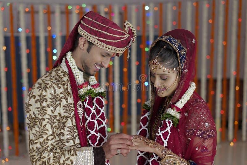 La jeune mariée indoue indienne et toilettent un couple de sourire heureux échangeant l'anneau de mariage. photographie stock