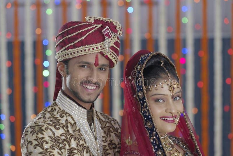 La jeune mariée indoue indienne et toilettent un couple de sourire heureux. photo libre de droits