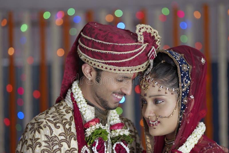 La jeune mariée indoue indienne et toilettent un couple de sourire heureux. images libres de droits