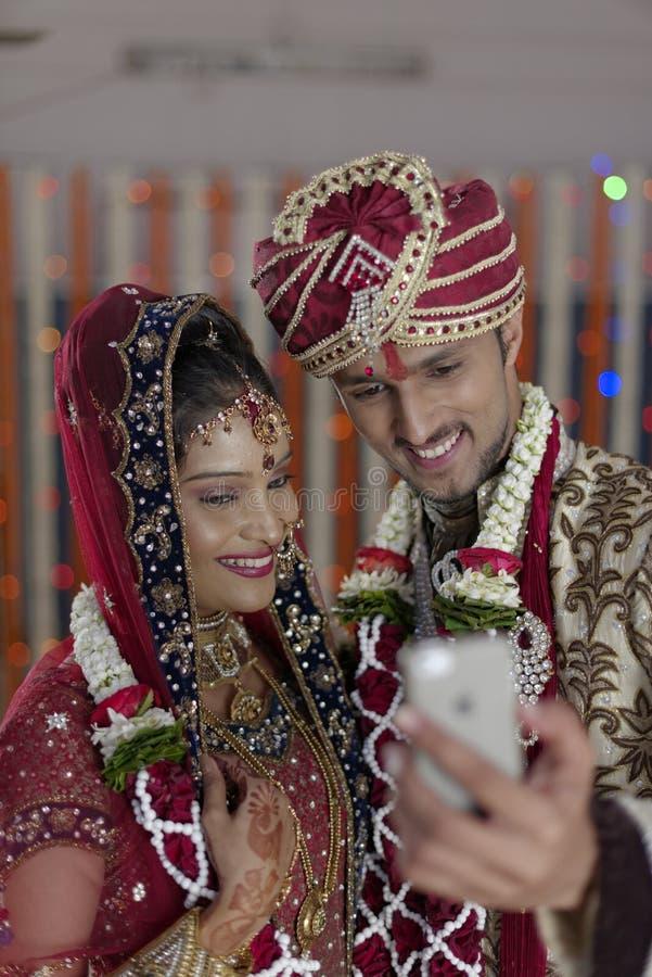 La jeune mariée indoue indienne et toilettent un individu de sourire heureux de tir de couples avec le mobile. photographie stock libre de droits