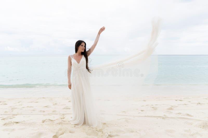La jeune mariée jette une robe blanche dans le ciel image libre de droits