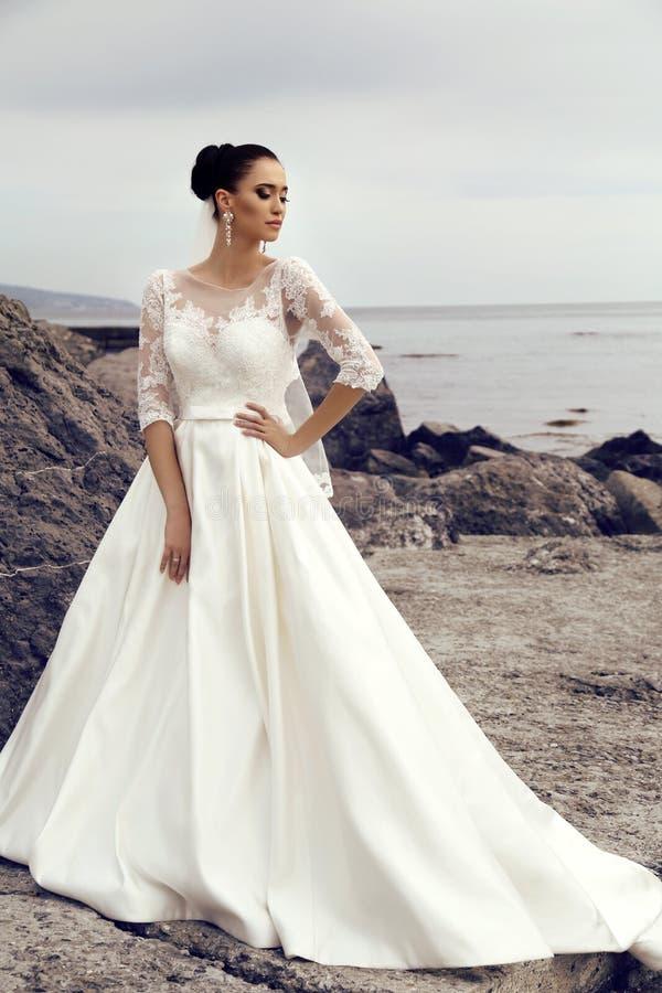 La jeune mariée magnifique avec les cheveux foncés porte la robe élégante de mariage images libres de droits