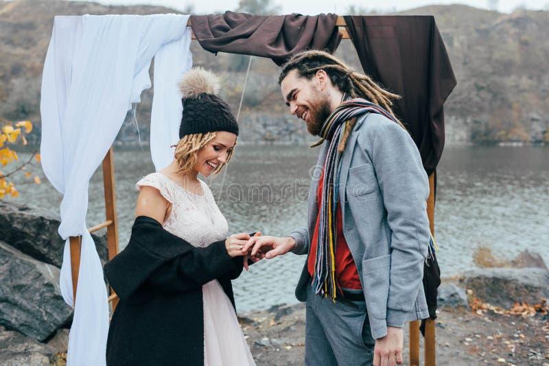 La jeune mariée met un anneau de mariage un moment de doigt du ` s de marié, heureux et joyeux Cérémonie de mariage d'automne deh photo libre de droits