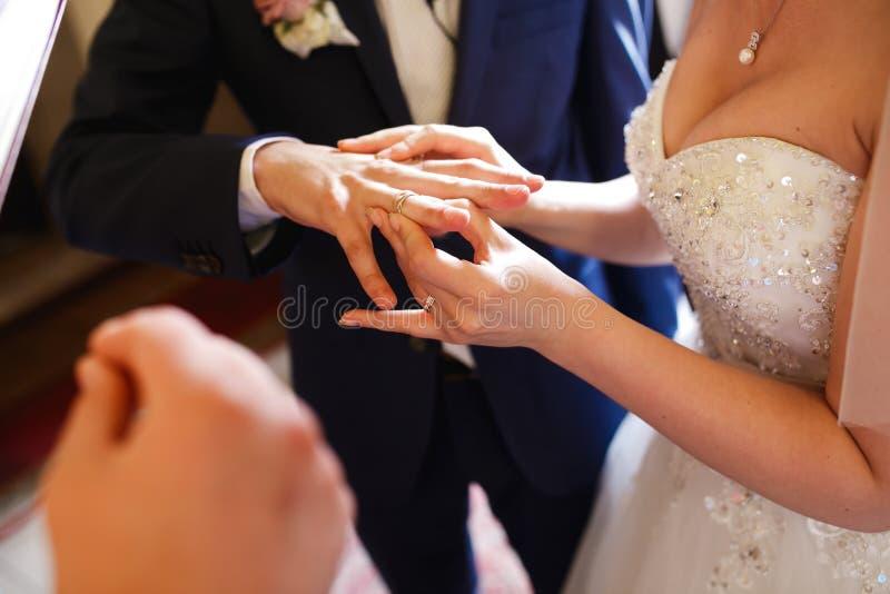 La jeune mariée met un anneau sur le doigt du marié délicatement image libre de droits