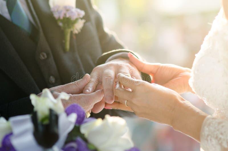La jeune mariée a mis l'anneau de mariage sur la main du marié image stock