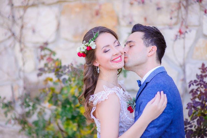 La jeune mariée renversante sourit tenant ses mains sur la veste bleue du ` s de marié photos libres de droits