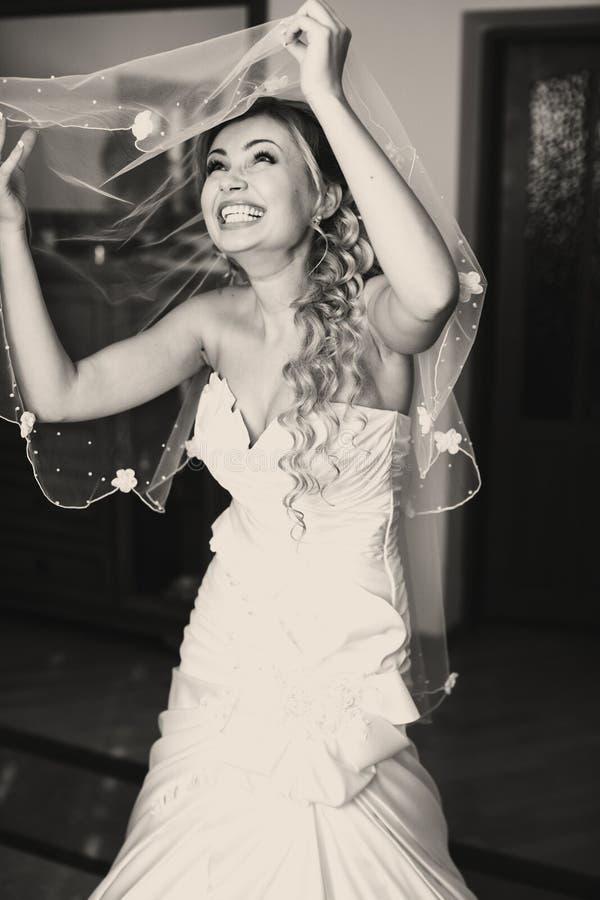 La jeune mariée rit sincèrement tout en mettant sur un voile photos stock