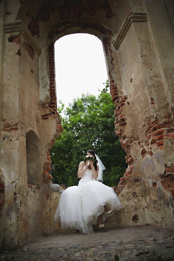 La jeune mariée s'assied sur les ruines et tient un bouquet de mariage image stock