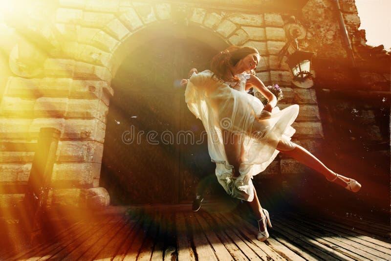 La jeune mariée saute dans le ciel avant un vieux château dans les rayons de soleil image libre de droits