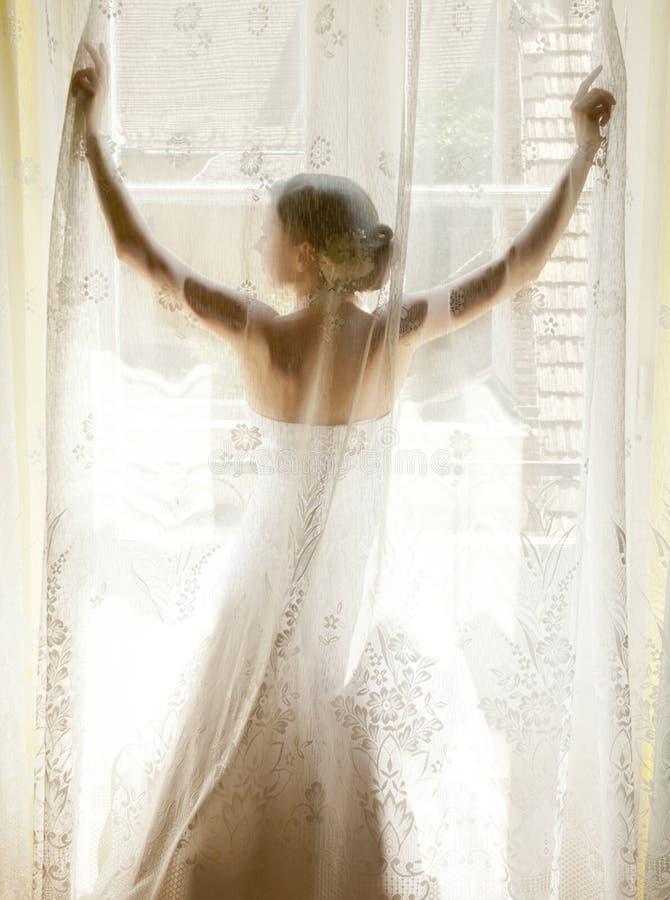 La jeune mariée se tenant sur la fenêtre photos stock