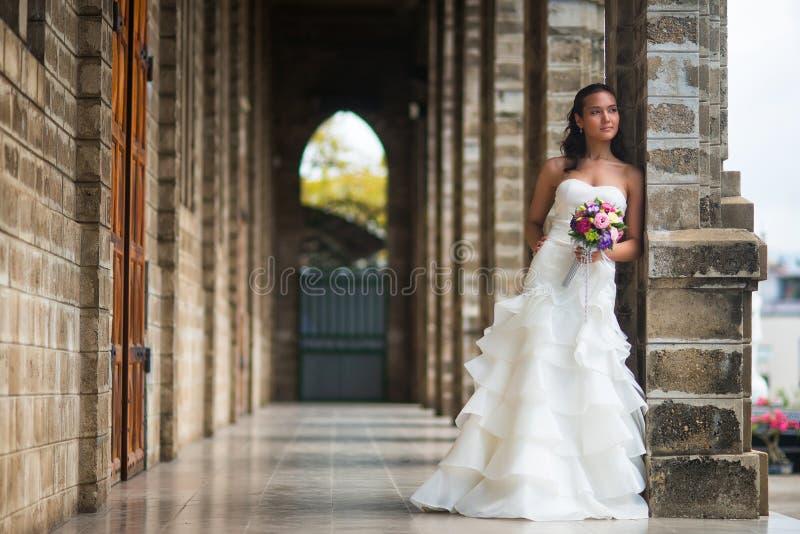 La jeune mariée se tient dans une galerie des murs en pierre dans une belle robe de mariage blanche avec un bouquet des fleurs images stock