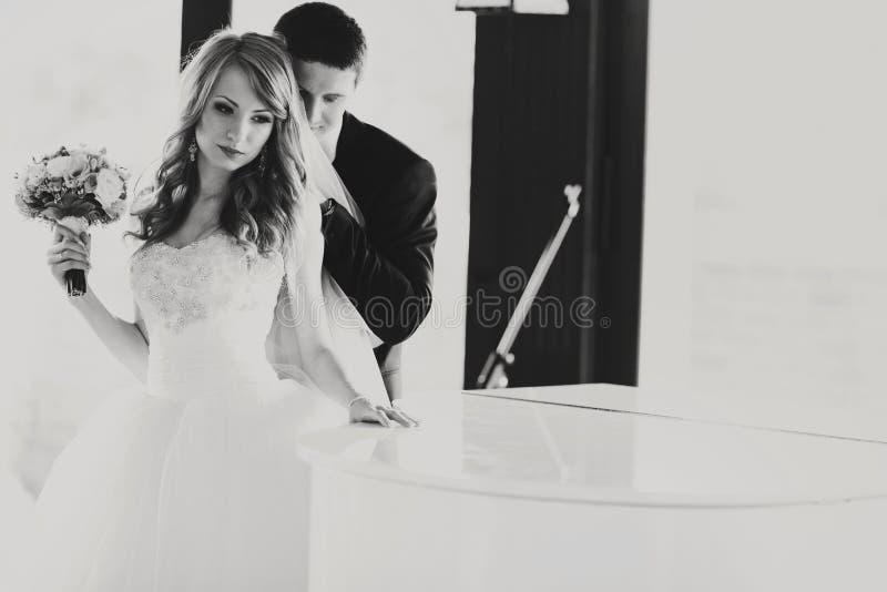 La jeune mariée se tient réfléchie derrière un piano tandis que le marié l'étreint de images libres de droits