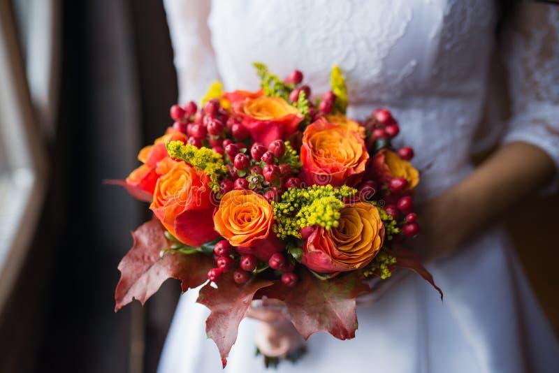 La jeune mariée tenant épouser le bouquet coloré de l'automne fleurit image libre de droits