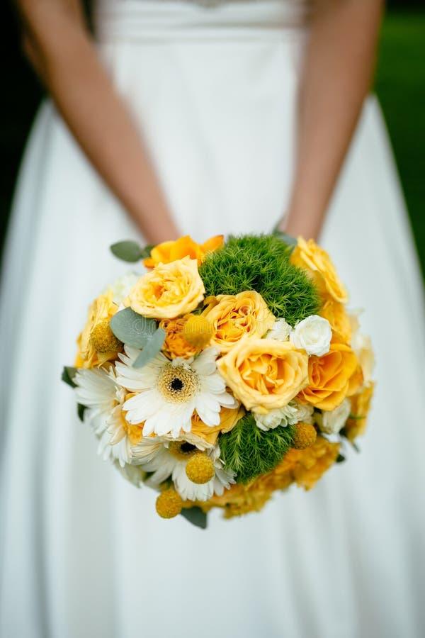 La jeune mariée tenant un bouquet avec les fleurs jaunes photo libre de droits