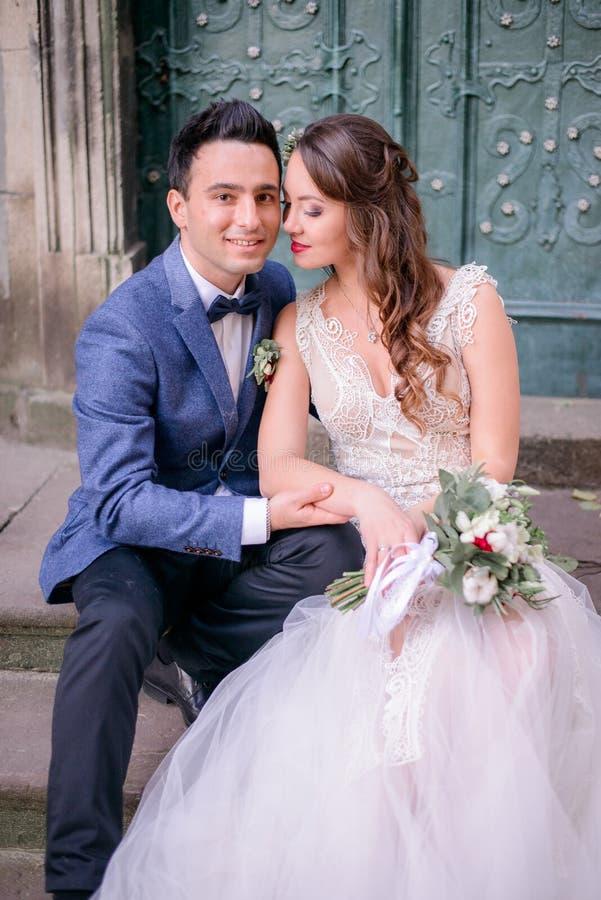 La jeune mariée tendre se trouve elle remettent le genou du ` s de marié image stock
