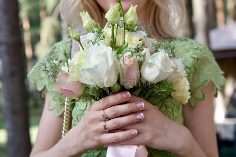 La jeune mariée tient dans des ses mains un bouque l'épousant images libres de droits