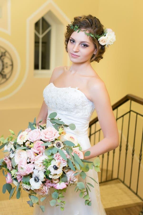 La jeune mariée tient un grand bouquet des fleurs photos stock