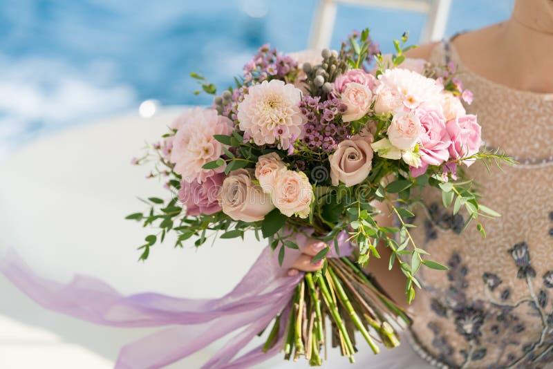 La jeune mariée tient un rose et un bouquet l'épousant lilas dans des ses bras dans la perspective de la mer images stock