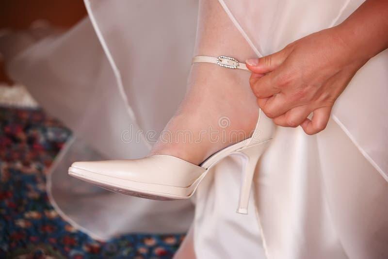 la jeune mariée touche la courroie des chaussures photos libres de droits