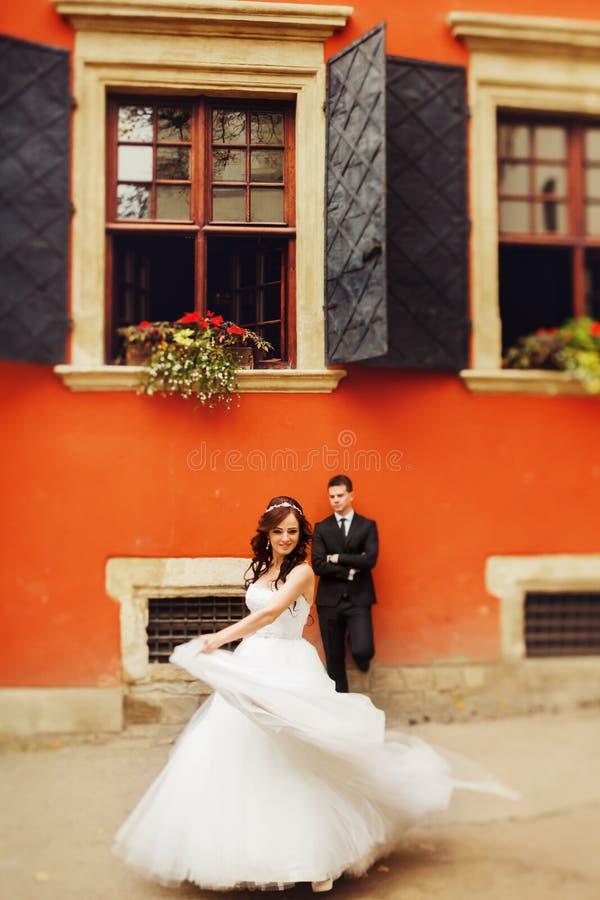 La jeune mariée tourbillonne avant un marié se tenant derrière une maison orange images libres de droits