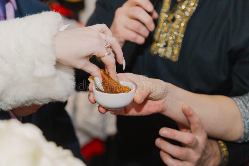 La jeune mariée trempe une tranche d'épouser le pain en sel image stock