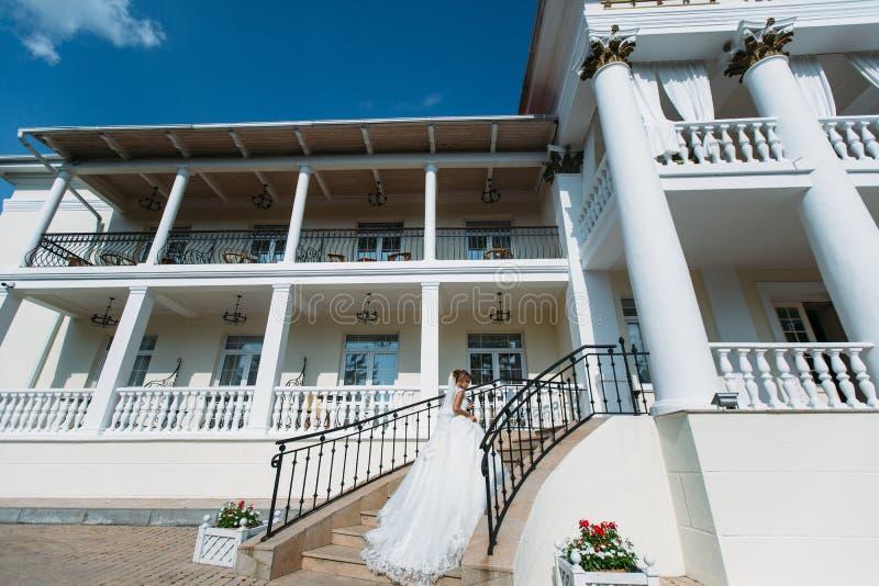 La jeune mariée va vers le haut des escaliers au bâtiment avec les colonnes Elle tient une jupe de sa robe de mariage blanche, un photos libres de droits