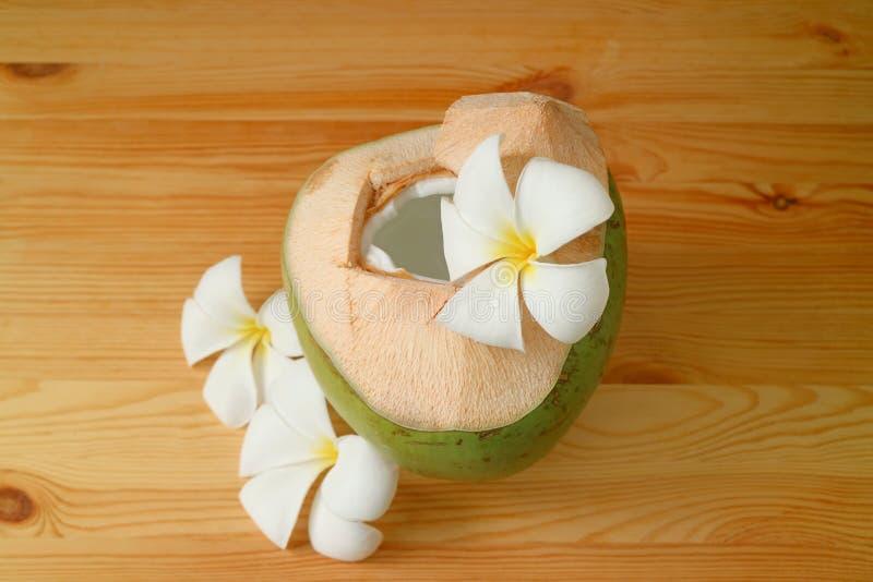 La jeune noix de coco fraîche avec de la viande savoureuse de jus et de fruit à l'intérieur a servi sur la table en bois avec des images libres de droits