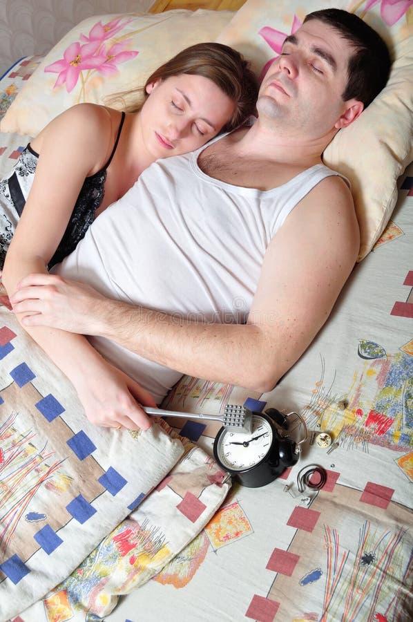 La jeune paire a cass? une horloge d'alarme images stock