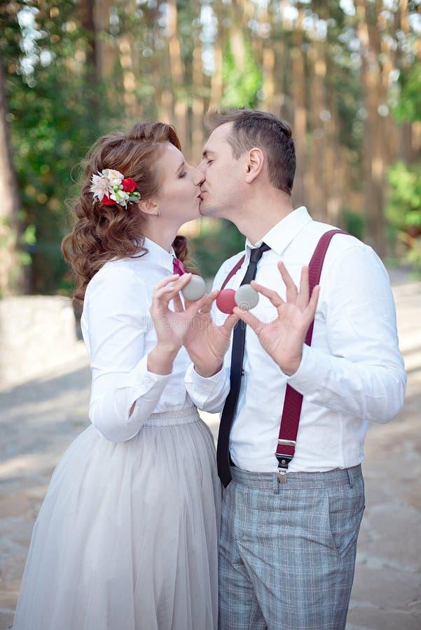 La jeune participation de couples a coloré des macarons sur les yeux image stock