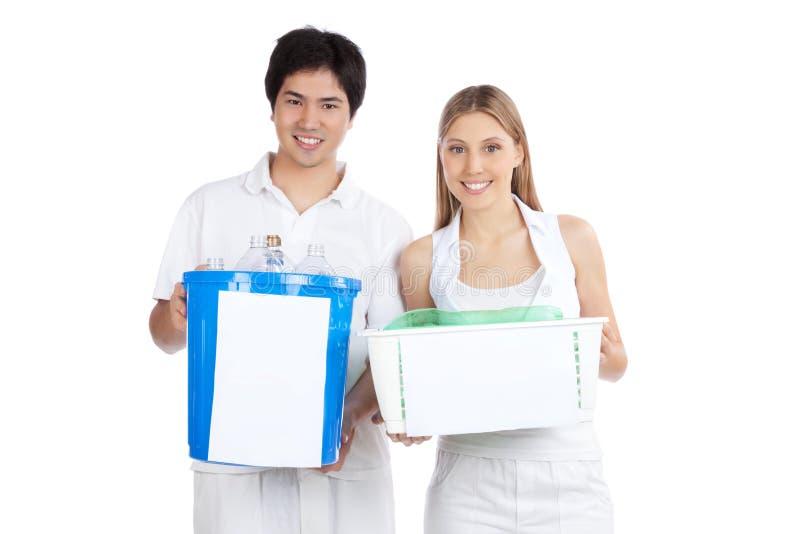 La jeune participation de couples réutilisent la poubelle photo stock