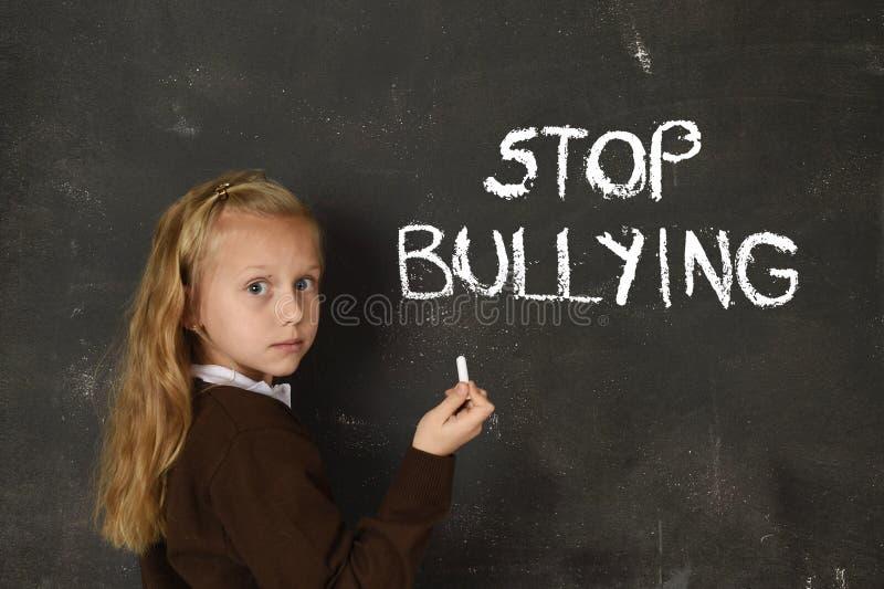 La jeune petite écolière mignonne a effrayé l'écriture triste le texte de intimidation d'arrêt de mots écrit avec la craie photographie stock