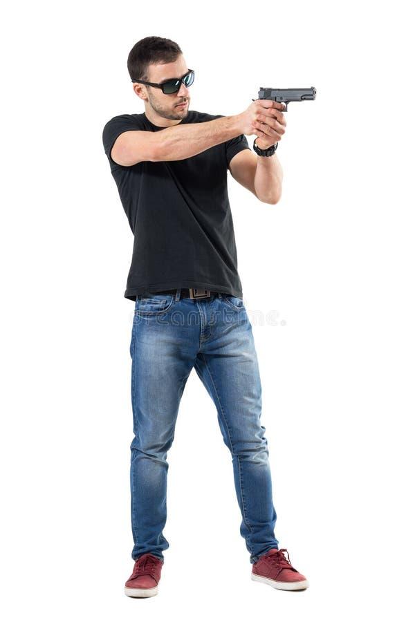 La jeune plaine vêtx le policier avec des lunettes de soleil visant l'arme à feu loin Vue de côté photographie stock