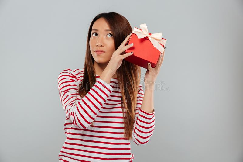 La jeune position asiatique sérieuse de dame a isolé tenir le cadeau image libre de droits