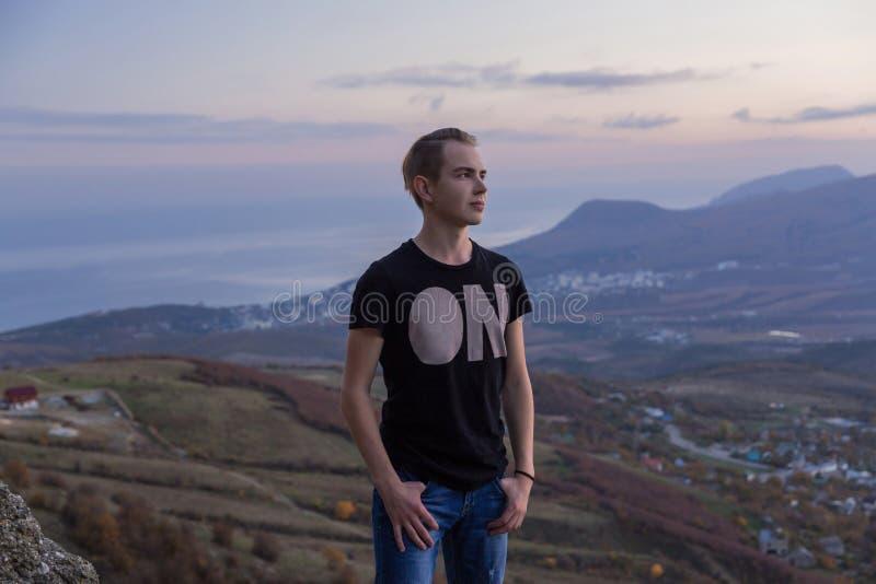 La jeune position attrayante d'homme sur le dessus des montagnes examine la distance image stock