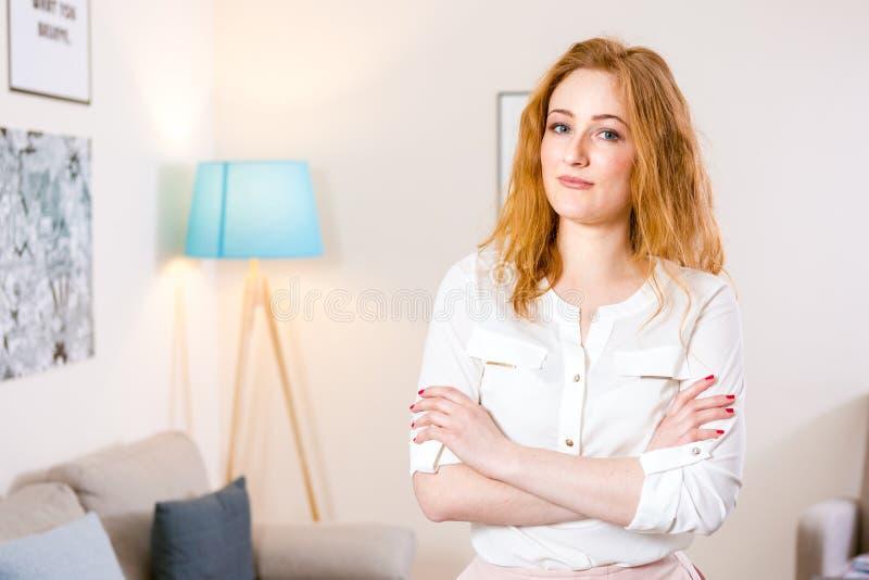 La jeune position caucasienne de fille dans le bureau et a pli? ses bras ? travers son coffre charmant la jeune fille travaille ? images stock