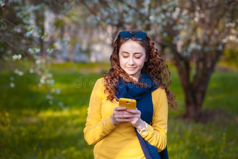 La jeune position smilling de femme dans un jardin de floraison et écrit au téléphone portable Cerise de floraison Verticale de b photos stock
