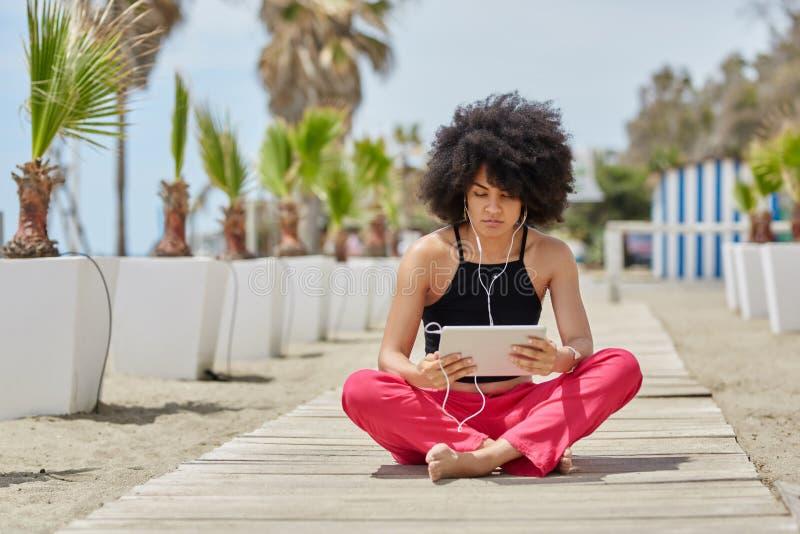 La jeune séance afro-américaine de femme a croisé la musique de écoute f de jambes photos stock