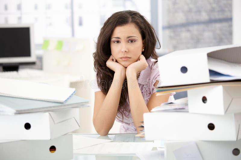 La jeune séance d'employé de bureau a préoccupé dans le bureau images stock