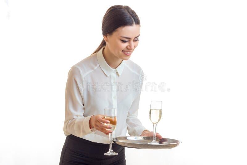 La jeune serveuse gaie avec des verres de vin sur un trey sourit photographie stock