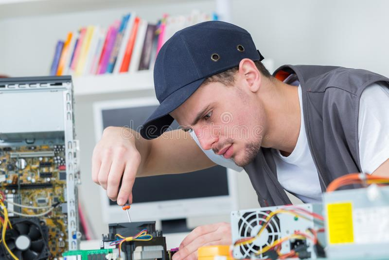La jeune technologie masculine examine le matériel électronique photographie stock