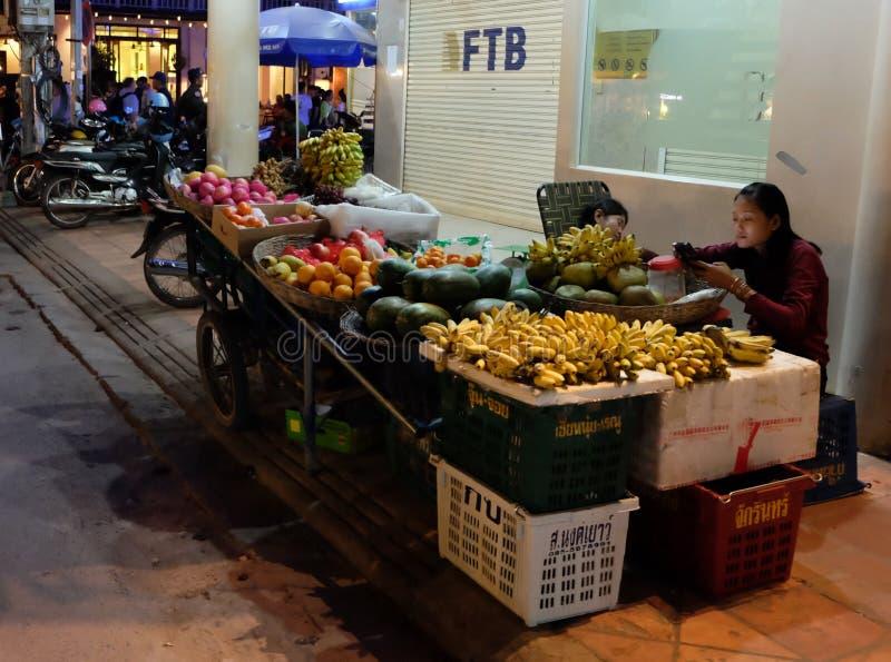 La jeune vendeuse asiatique de fille des bananes sur la rue de la ville de nuit regarde dans le smartphone images stock